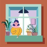 kvinna som ser ut genom fönstret med fasaden på byggnaden