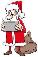 Weihnachtsmann-Zeichentrickfilmfigur des Weihnachtsmannes mit Tablette pc vektor