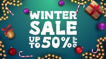Winterverkauf, grünes Rabattbanner mit Weihnachtskugeln