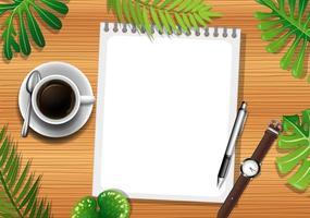 ovanifrån av träbord med blankt papper och kontorsobjekt och bladelement