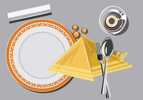 Närbild på tallrik med sked och gaffel och servett