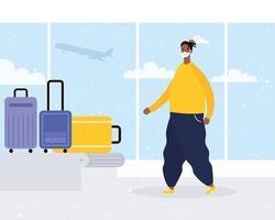 Afro junger Mann, der medizinische Maske mit Koffern im Transportband trägt