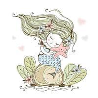 Eine süße kleine Meerjungfrau sitzt auf einem Felsen