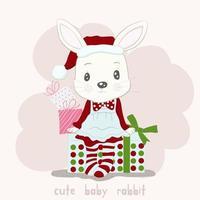 süßes kleines Kaninchen in der Weihnachtsmütze, die auf Geschenken sitzt