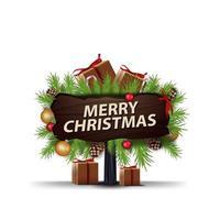 Frohe Weihnachten, Holzzeiger mit Rahmen von Weihnachtsbaumzweigen verziert mit Geschenken und Zuckerstangen. hölzernes Grußzeichen lokalisiert auf Weiß