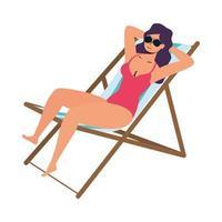 schöne Frau, die Badeanzug trägt und im Strandkorb sitzt