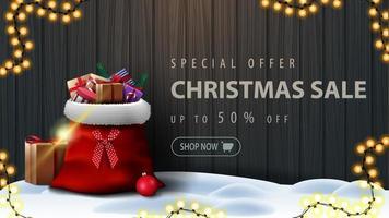 Sonderangebot, Weihnachtsverkauf, bis zu 50 Rabatt, Rabatt-Banner mit Holzzaun aus Brettern mit Rahmen aus Weihnachtsbaumzweigen, Girlande aus gelben Glühbirnen und Weihnachtsmann-Tasche mit Geschenken