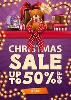 Weihnachtsverkauf, bis zu 50 Rabatt, lila vertikale Rabatt-Banner mit rotem horizontalen Band mit Schleife, Girlande und Geschenken mit Teddybär vektor