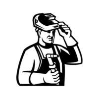 Schweißer hält Schweißbrenner, der das Visiermaskottchen in Schwarzweiss anhebt