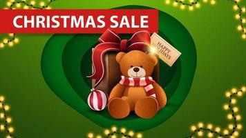 Weihnachtsverkauf, grünes Rabattbanner im Papierschnittstil, Girlande und Geschenk mit Teddybär vektor