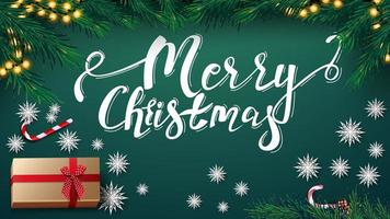 Frohe Weihnachten, grüne Postkarte mit Girlande, Weihnachtsbaum, Geschenk, Papierschneeflocken und Zuckergussdose, Draufsicht