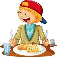 ein Junge, der Mahlzeit am Tisch auf weißem Hintergrund hat
