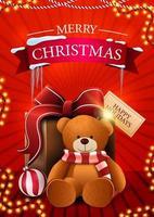 Frohe Weihnachten, rote vertikale Postkarte mit Girlande und Geschenk mit Teddybär