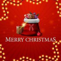 Frohe Weihnachten, rote quadratische Postkarte mit roter Weihnachtsmanntasche mit Geschenken