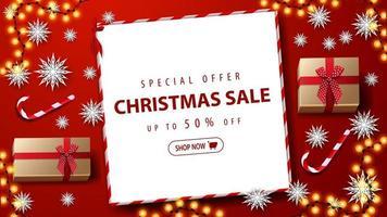 Sonderangebot, Weihnachtsverkauf, bis zu 50 Rabatt. rotes Rabattbanner mit Geschenken, Zuckerstangen, Papierschneeflocken, Girlande und weißem Papierblatt mit Angebot auf rotem Tisch, Draufsicht