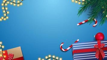Geschenke, Zuckerstangen, Weihnachtsbaumzweig und Girlande auf blauem Tisch, Draufsicht. Hintergrund für Rabattbanner oder Grußpostkarte