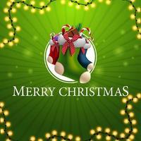 Frohe Weihnachten, quadratische grüne Grußkarte mit Girlande und Weihnachtsstrümpfen