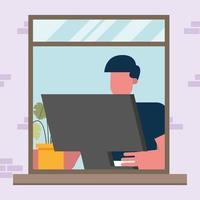 Mann arbeitet an einem Computer am Fenster