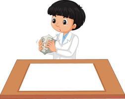 Ein Junge im Wissenschaftlerkleid mit leerem Papier auf dem Tisch