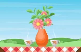 koppar te och vas med blommor på ett bord med utsikt över naturen