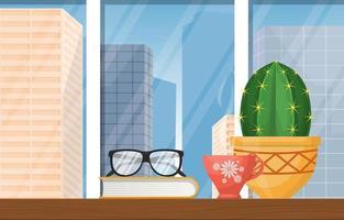 varmt te, kaktus och bok på bordet med stadens silhuett