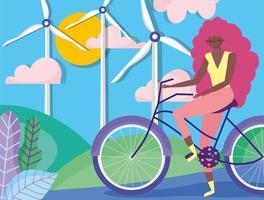 Frau, die Fahrrad durch Windturbinen und Sonnenkollektoren fährt