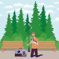 junger Mann, der niedliches Hundemaskottchen im Park anhebt vektor