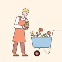 ein Mann in einer Schürze, der Blumen in einer Schubkarre trägt