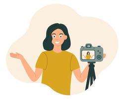 Das Blogger-Mädchen lächelt und deutet vor die Kamera, um das Video aufzunehmen. Vektorillustration im flachen Stil vektor