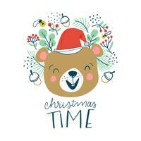 Netter Bär, der mit Weihnachtshut und -blättern lächelt.