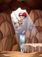 Pojke abseiling i grotta