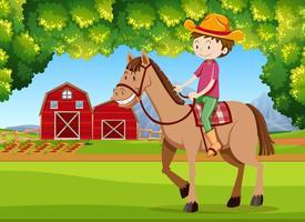 En pojke ridande häst på jordbruksmark