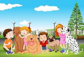 Barn och deras hundar i parken