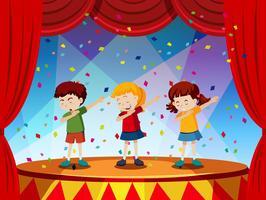 Grupp av barn utför på scenen