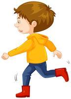 Liten pojke i gul jacka och röda stövlar
