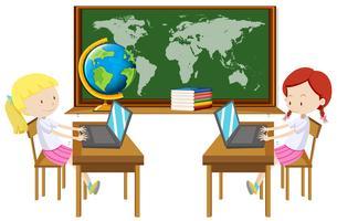 Mädchen zwei, das an Computer im Klassenzimmer arbeitet