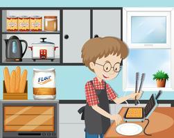 En man matlagningsvaffel i köket