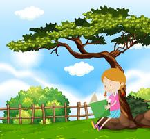 En tjej som läser en bok under träd