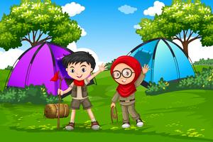Pojke och flicka scout camping i skogen