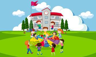 Barn som leker med fallskärm framför skolan