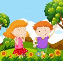 Pojke och tjej som leker i trädgården