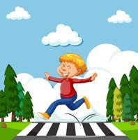 En glad pojke som korsar vägen