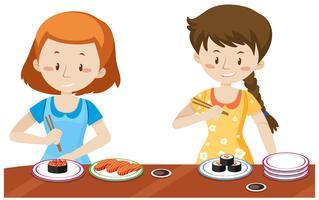 Flickor äter japanska Sushi