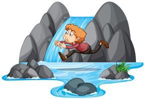 En pojke hoppar på klippan