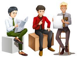 Tre män sitter ner medan de läser, pratar och håller en tom kartong