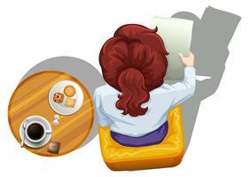 En toppvy av en kvinna som läser bredvid bordet