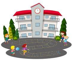Barn spelar hopscotch framför en skola
