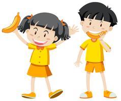 Pojke och tjej i gul outfit med banan