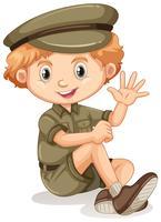 Ein glücklicher Junge, der in einer Safariausstattung sitzt vektor