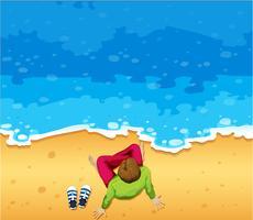 Man sitter på stranden